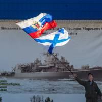 A pro-Russian activist waves the Russian state and navy flags outside an entrance to the General Staff Headquarters of the Ukrainian Navy in Sevastopol, Ukraine, on Monday.  | AP