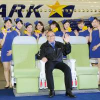 Shinichi Nishikubo, president of Skymark Airlines Inc., sits in an Airbus A330 on Friday as cabin attendants in miniskirt uniforms stand by. | KYODO