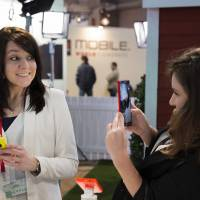 A woman takes a picture with a Nokia Lumia 1520 phone as her friend smiles at the Mobile World Congress in Barcelona, Spain, on Tuesday. Companies are making photography and photo manipulation easier to do on phones as image quality approaches that of digital single-lens reflex cameras. | AP
