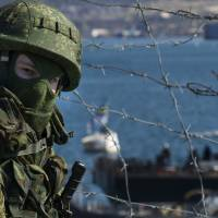 A Russian soldier guards a pier where two Ukrainian naval ships are moored, in Sevastopol, Ukraine, on Wednesday.   AP