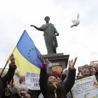 Ukrainian women hold a national flag with EU stars while releasing birds as a symbol of peace after singing the national anthem during an anti-war protest in the Black Sea port of Odessa, Ukraine, on Sunday. | AP