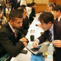 Personnel representatives from Japanese companies talk with Saudi Arabian students at a job fair organized by the Saudi Arabian Embassy in Tokyo Thursday. It is rare for an embassy to help its own citizens find jobs while they are in Japan. | KYODO
