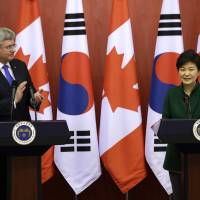Canadian Prime Minister Stephen Harper applauds while South Korean President Park Geun-hye speaks during a news conference in Seoul after their nations reached a free trade agreement Tuesday. | AP