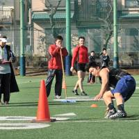 Survival of the fittest: Deers offensive coordinator Gen Arisawa (left) runs the rule over a participant in the team's tryout on Saturday in Chofu, Tokyo. | HIROSHI IKEZAWA