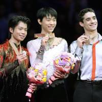 Their time to shine: Gold medalist Yuzuru Hanu (center), compatriot Tatsuki Machida (left), who claimed the silver, and Spain's Javier Fernandez, the bronze medalist, share the spotlight on the podium on Friday. | KYODO