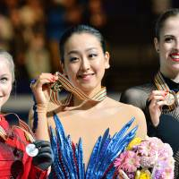Center stage: Gold medalist Mao Asada (center), silver medalist Julia Lipnitskaia of Russia (left) and third-place finisher Carolina Kostner of Italy attend the award ceremony on Saturday night. | AFP-JIJI