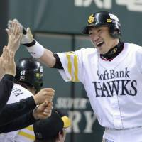 Reason to rejoice: The Hawks' Seiichi Uchikawa is congratulated by teammates after slugging a solo home run to lead off the eighth inning on Sunday against the Marines. Fukuoka Softbank defeated Chiba Lotte 3-2. | KYODO