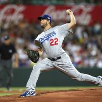 Let's get it started: Los Angeles' Clayton Kershaw throws the first pitch of the 2014 MLB season against the Diamondbacks in Sydney on Saturday night. The Dodgers won 3-1. | AP