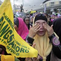 Filipino Muslims wipe away tears after learning that a peace accord was signed between Moro Islamic Liberation Front leaders and Philippine President Benigno Aquino III, at a rally on Thursday outside the presidential palace in Manila. The deal was brokered by Malaysia. | AP