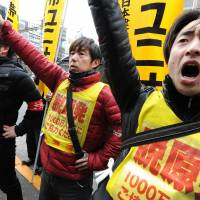 Workers from the Fukushima No. 1 nuclear plant and their supporters shout slogans and raise their fists in front of the headquarters of Tokyo Electric Power Co. on Friday. | AFP-JIJI