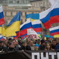 Some 50,000 protesters carry Ukrainian and Russian national flags in central Moscow on Saturday during a rally against Russia's intrusion in Crimea, southern Ukraine, on the eve of a vote expected to see the peninsula switch to Russian rule. | AFP-JIJI