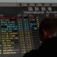 The arrival board at Beijing airport lists flight MH370 from Kuala Lumpur in red (top) after a Malaysia Airlines Boeing 777-200 disappeared Saturday with 239 on board. The airline was already notifying next of kin, in a sign that it feared the worst. | AFP-JIJI