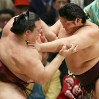 First one out of the way: Endo (right) grapples with ozeki Kisenosato on Thursday. | KYODO