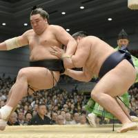 Business as usual: Yokozuna Harumafuji is ushered out of the ring by Kakuryu during Spring Grand Sumo Tournament in Osaka on Thursday. | KYODO