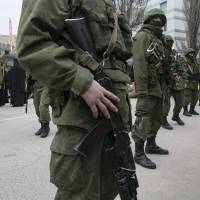 Armed servicemen stand near a Ukrainian border guard post in the Crimean town of Balaclava on Saturday. | REUTERS