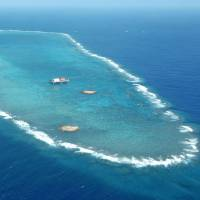 The tiny disputed outcroppings that represent Okinotorishima Island, an atoll some 1,700 km south of Tokyo and about 1,000 southeast of Okinawa, is shown April 2005 before high tide. | KYODO