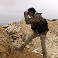 In this photo provided by a local anti-government activist group, a Syrian rebel looks through his binocular at one of the front-line town of Yabroud, which had been the final rebel stronghold in Syria's mountainous Qalamoun region, on Thursday. | AP