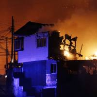 A group of firefighters stand next to burning homes as a forest fire rages Sunday toward urban areas in the city of Valparaiso, Chile. | AP