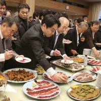 Attendees to a pro-whaling event held Tuesday in Tokyo help themselves to a buffet featuring whale meat.  | AP