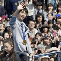 Golden child: Yuzuru Hanyu waves to fans during a parade in Sendai. | KYODO