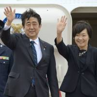 Prime Minister Shinzo Abe and his wife, Akie, wave to onlookers at Tokyo's Haneda airport on Tuesday before boarding a plane bound for Europe. | KYODO
