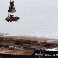 A bulldozer is unloaded Tuesday from the Baosteel Emotion, owned by Mitsui O.S.K. Lines, at a port in Zhejiang province, China. A Chinese maritime court seized the ship Saturday. | REUTERS