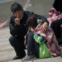 Relatives of a passenger on board the sunken South Korean ferry Sewol weep at Jindo harbor on Tuesday. | AFP-JIJI
