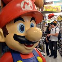 A large Super Mario character stands inside a video game retailer as customers browse for goods on Thursday. Nintendo's Game Boy celebrates its 25th anniversary Monday. | AFP-JIJI