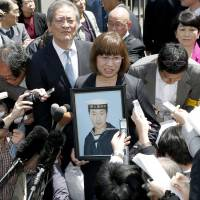 The mother of an MSDF seaman who committed suicide due to abuse meets reporters at the Tokyo High Court on Wednesday. | KYODO