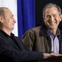 U.S. President George W. Bush shares a laugh with Russian President Vladimir Putin as the two answer questions at a high school in Crawford, Texas, in November 2001. | REUTERS