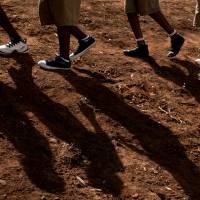 Rwandan children walk to a torch ceremony symbolizing remembrance and to hear genocide victims recount their memories at the Petit Seminaire school in Ndera, east of the capital, Kigali, on Thursday. | AP
