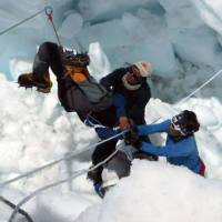 Nepalese rescue team members help an avalanche survivor on Mount Everest on Friday. | AFP-JIJI