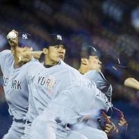 So it begins: Yankees starter Masahiro Tanaka pitches against the Blue Jays in the first inning on Friday in Toronto. Tanaka earned the win in his MLB debut.   AP