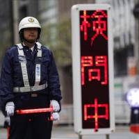 A police officer mans a checkpoint Tuesday, the day before U.S. President Barack Obama was to arrive in Tokyo. | REUTERS