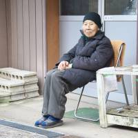 Mrs. Aizawa sits outside the colony's communal dining hall. | MARK BUCKTON