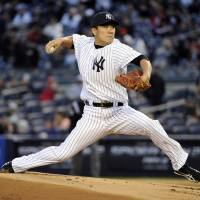 First home start: New York's Masahiro Tanaka fires a pitch against Baltimore in the first inning on Wednesday night. | AP