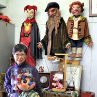 Wall of fame: PUK's international liaison, Tamiko Onagi, poses in a puppets' dressing room. | YOSHIAKI MIURA
