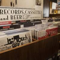 Now playing: A sign on the record rack at Big Love Records points the way to music and drinks. | CHIEKO KATO