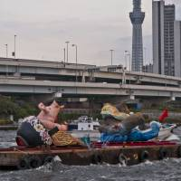 Making waves: A portable shrine created by Tokyo University of the Arts students under an ACT pilot program is paraded on the Sumida River near Tokyo SkyTree in the city's downtown during an evening-sun festival in October 2013. | © SHIHO KITO