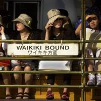 Safety in numbers: Japanese tourists sit on the Waikiki Trolley in Honolulu. Group tours shield travelers to a degree from the reality of being a foreigner abroad, an experience that might otherwise help them empathize with outsiders in their home country. | AP