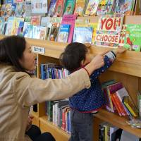 Pick and choose: A mother helps her child select an English-language book from a selection that has become a big draw card for Iwakura Public Library. | NOZOMI IKEDA