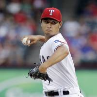Roughed up: Texas starter Yu Darvish fires a pitch against Oakland in the first inning on Monday night. | AP