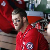 Early exit: Washington's Bryce Harper sits on the bench during Saturday's game against St. Louis. The Cardinals edged the Nationals 4-3.   AP