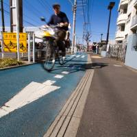 Separation of powers: A cyclist rides past a bus stop on the Kaede-dori bike track in Tokyo's Musashino neighborhood in March. | JAMES HADFIELD PHOTO
