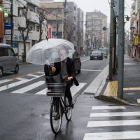 Mean streets: A man uses an umbrella while cycling down Waseda-dori in Koenji, Suginami Ward, in March. | JAMES HADFIELD PHOTO