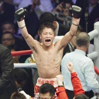 Top of the world: Naoya Inoue raises his arms in triumph after winning the WBC light flyweight world title. | KYODO