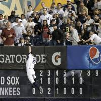 Go up and get it: The Yankees' Ichiro Suzuki makes a leaping catch to take a hit away from the Red Sox's David Ortiz on Sunday in New York. The Yankees defeated the Red Sox 3-2. | AP