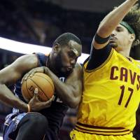 Cat Scratch Fever: The Bobcats' Al Jefferson (left) grabs a rebound against Cavaliers center Anderson Varejao during their game on Saturday in Cleveland. | AP