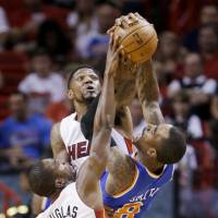 Block party: Knicks guard J.R. Smith has his shot contested by the Heat's Udonis Haslem and Toney Douglas during Miami's 102-91 victory on Sunday. | AP