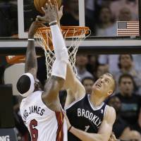 Point of contention: Brooklyn's Mason Plumlee (right) blocks LeBron James in the final seconds of Tuesday's game. | AP